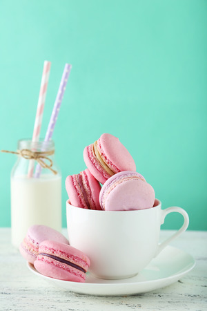 French macarons in cup on white wooden background photo