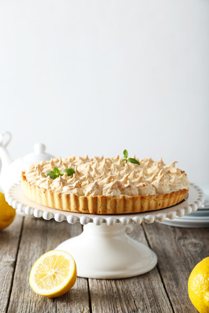 recipe decorated: Lemon meringue pie on cake stand on grey wooden background