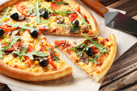 peice: Fresh tasty pizza on brown wooden background
