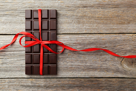 Dark chocolate bar with red bow on grey wooden background