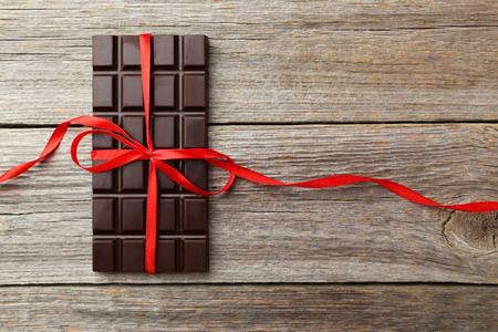 barra: Barra de chocolate negro con un lazo rojo sobre fondo de madera gris Foto de archivo