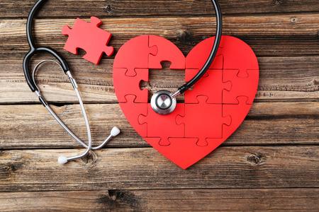 ataque al corazón: Corazón rojo del rompecabezas con el estetoscopio en el fondo de madera marrón