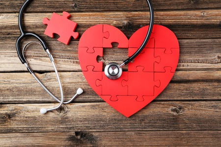 Red puzzle heart with stethoscope on brown wooden background photo