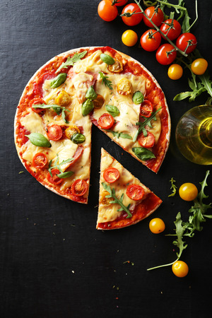 amarillo y negro: Sabrosa pizza fresca en el fondo negro
