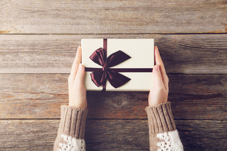 holding: Female hands holding gift box on grey wooden background