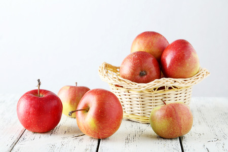 Apples in basket on white wooden background photo