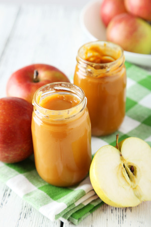 Jars of baby puree with apples on white wooden background photo