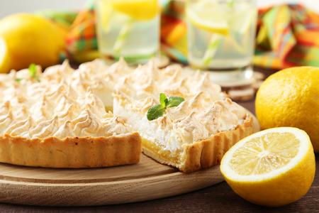 pie: Lemon meringue pie on cutting board on brown wooden background