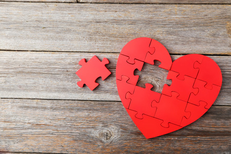 puzzle background: Red puzzle heart on grey wooden background