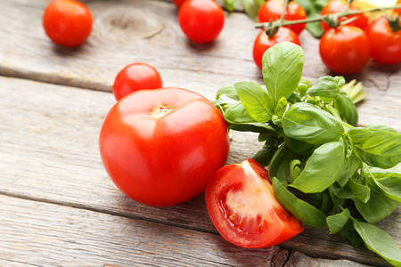 peice: Tomatoes and basil leaves on grey wooden background