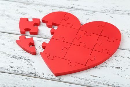 Red puzzle heart on white wooden background photo