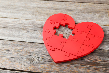 Red puzzle heart on grey wooden background photo