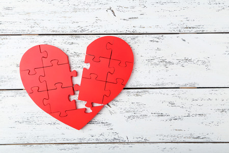 broken relationship: Red puzzle heart on white wooden background Stock Photo