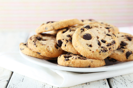 Chocolate chip cookies on plate on white wooden background Standard-Bild