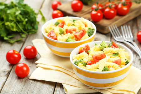 pasta dish: Delicious pasta in bowls on grey wooden background