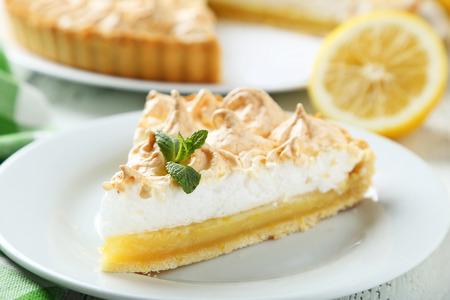 pie de limon: Pastel de limón en un plato sobre fondo de madera blanca