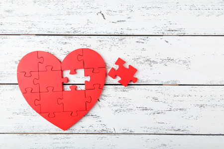 Red puzzle heart on white wooden background 版權商用圖片