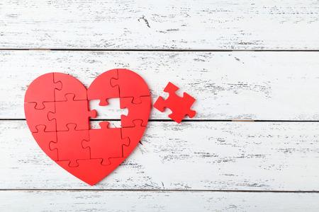 Red puzzle heart on white wooden background Standard-Bild