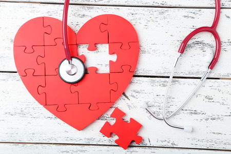 murmur: Red puzzle heart with stethoscope on white wooden background
