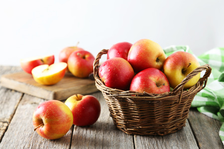 cesta de frutas: Manzanas rojas en la cesta sobre fondo de madera gris