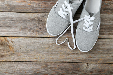 athletic wear: Pair of grey shoes on wooden background