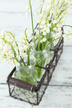 Lily of the Valley in bottles on white wooden background photo