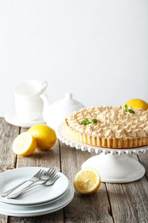 stand teapot: Lemon meringue pie on cake stand on grey wooden background