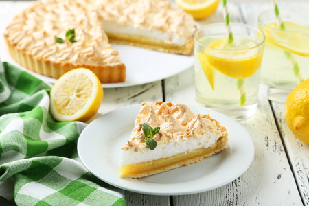 lemon: Lemon meringue pie on plate on white wooden background