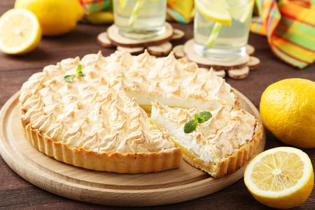 Lemon meringue pie on cutting board on brown wooden background