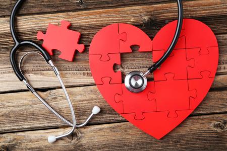 ataque cardiaco: Corazón rojo del rompecabezas con el estetoscopio en el fondo de madera marrón