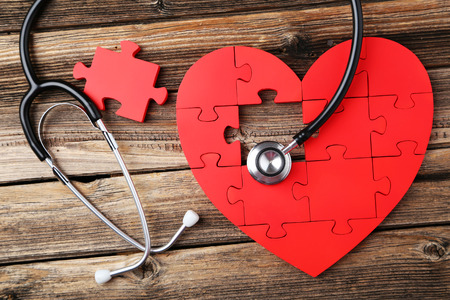 puzzle: Red puzzle heart with stethoscope on brown wooden background Stock Photo