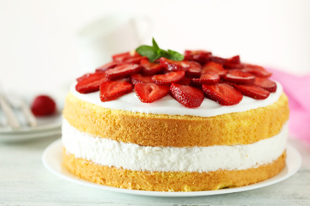 Sweet cake with strawberries on plate on white wooden background
