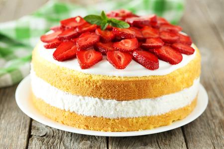 Zoete cake met aardbeien op plaat op grijze houten achtergrond Stockfoto