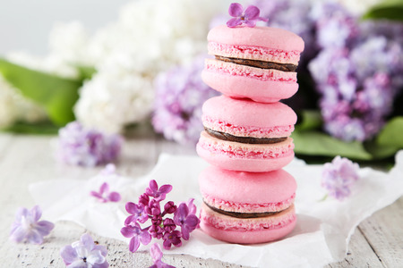 strawberry jam sandwich: French pink macarons with lilac flowers on white wooden background Stock Photo