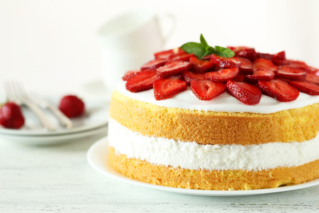 sweet tart: Sweet cake with strawberries on plate on white wooden background