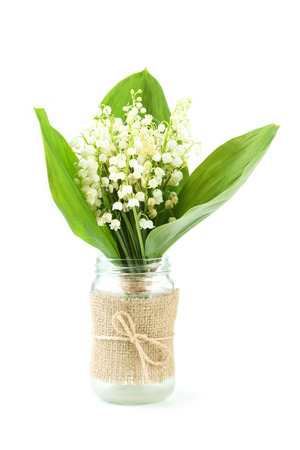 mayflower: Lily of the Valley in bottle isolated on white