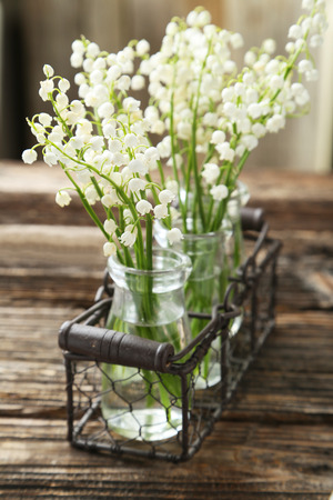 mayflower: Lily of the Valley in bottles on brown wooden background Stock Photo