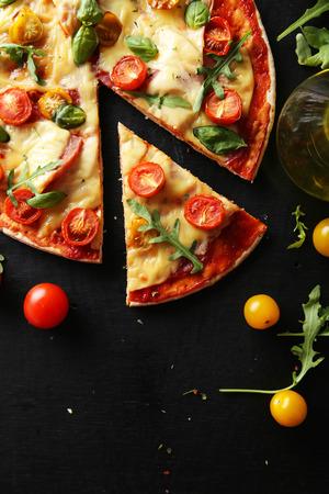 Verse smakelijke pizza op een zwarte achtergrond Stockfoto