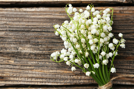 mayflower: Lily of the Valley on brown wooden background