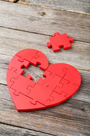 Red Puzzle Herz auf weißem Holzuntergrund