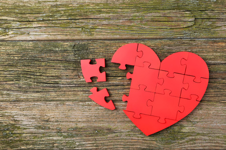 Red puzzle heart on wooden background photo