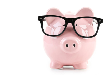Pink piggy bank with glasses isolated on a white Foto de archivo