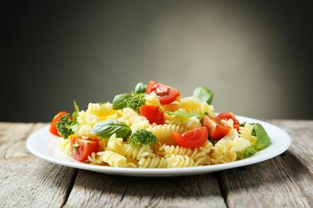 ensalada de tomate: Deliciosa pasta en un plato sobre fondo de madera gris