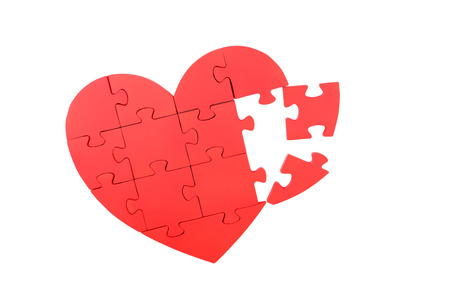 broken relationship: Red puzzle heart isolated on white