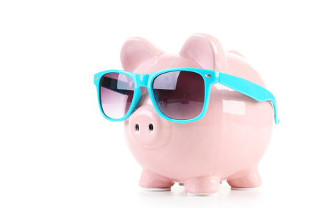 Pink piggy bank with glasses isolated on a white Standard-Bild