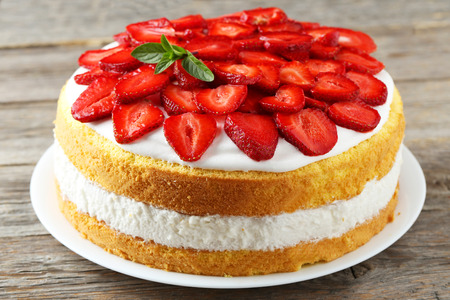 Sweet cake with strawberries on plate on grey wooden background