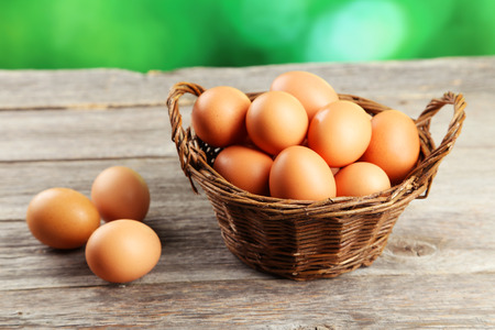 Chicken eggs in basket on grey wooden background