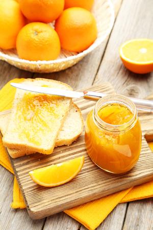 Bread and orange jam on grey wooden background photo