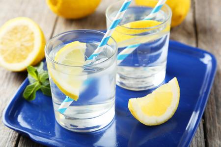vasos de agua: Limonada fresca con limón sobre fondo de madera gris