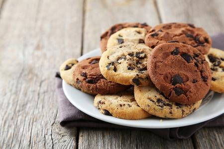 galletas: Galletas de chocolate en un plato sobre fondo de madera gris